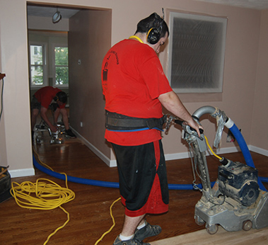 An employee polishing a new hardwood floor installation in Pelham, NH